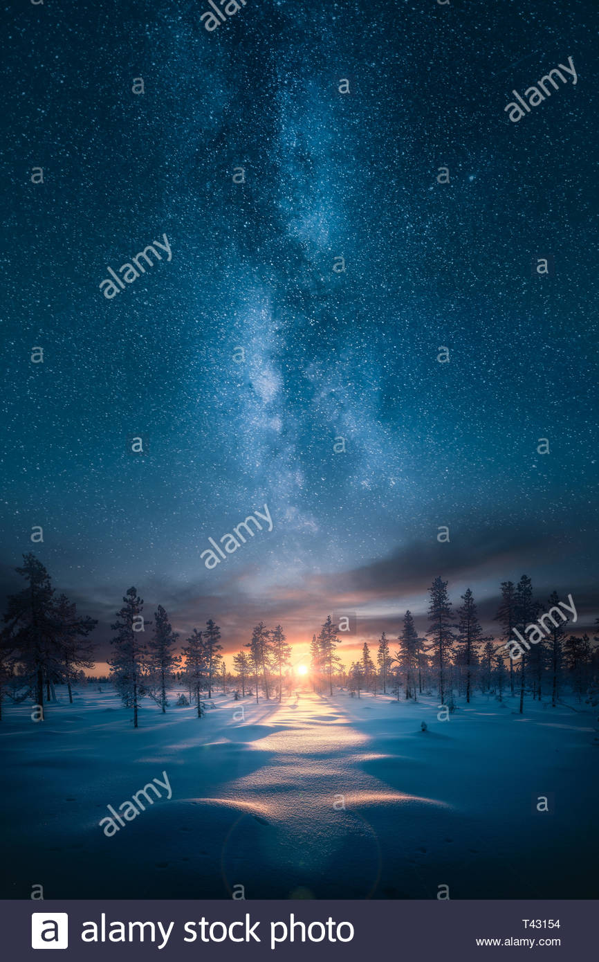 Ethereal fantasy image of sunset behind snowy  forest landscape with epic milky way on the sky - Stock Image