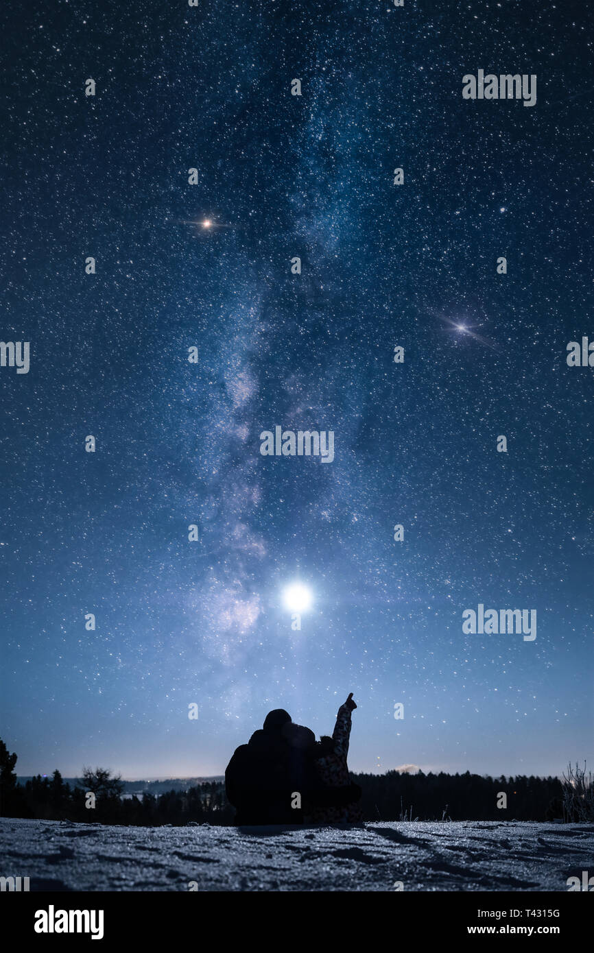 Silhouette of a couple sitting on snow at winter night and looking at the moon and stars. - Stock Image