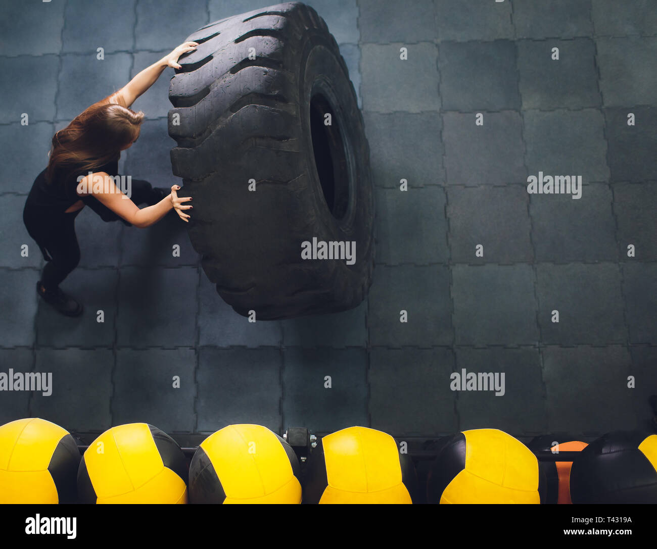 Fit female athlete working out with a huge tire, turning and carry in the gym. woman exercising with big tire. - Stock Image