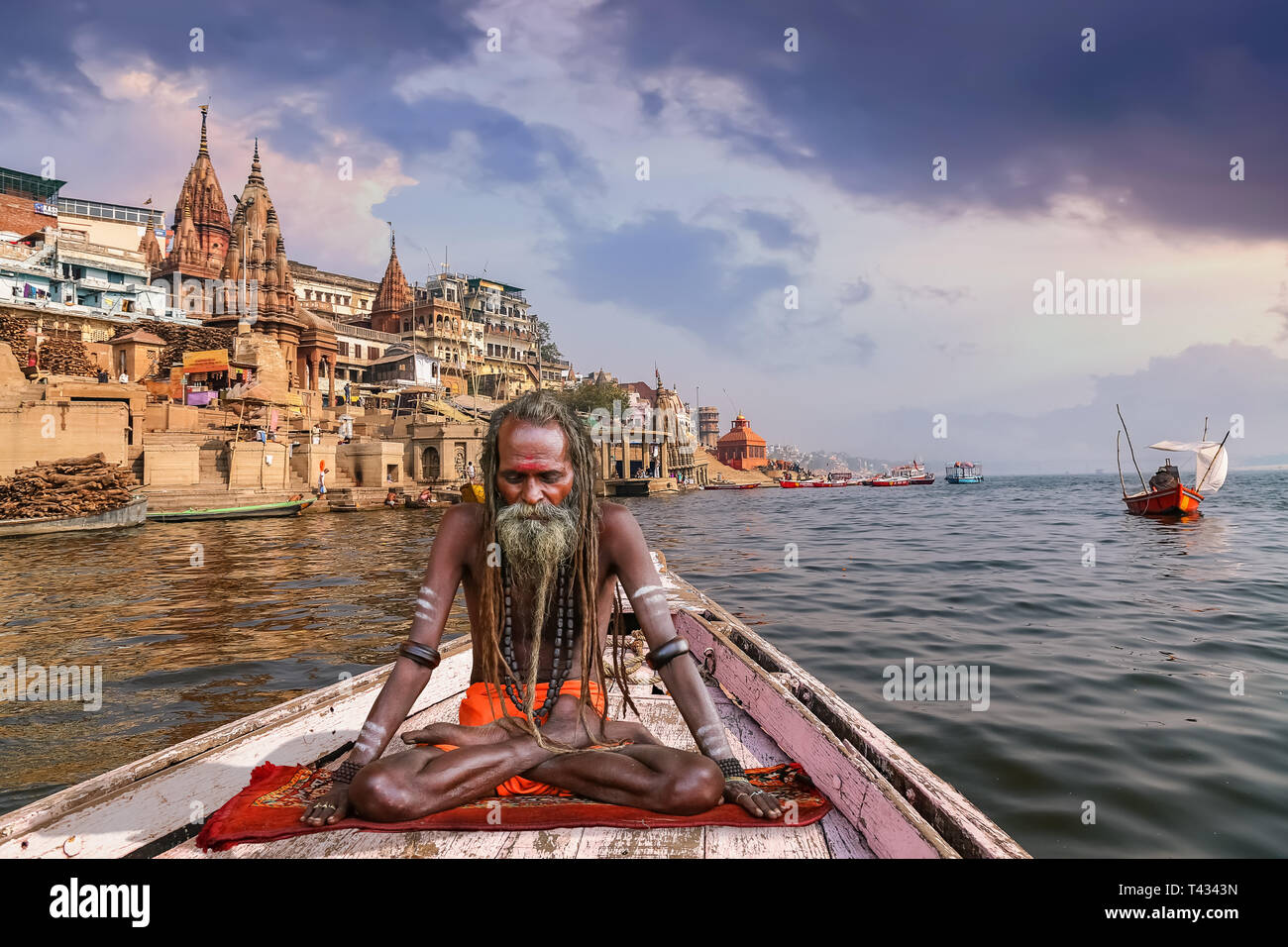 Sadhu baba in meditation posture on a wooden boat on river Ganges overlooking the Varanasi city at sunset - Stock Image