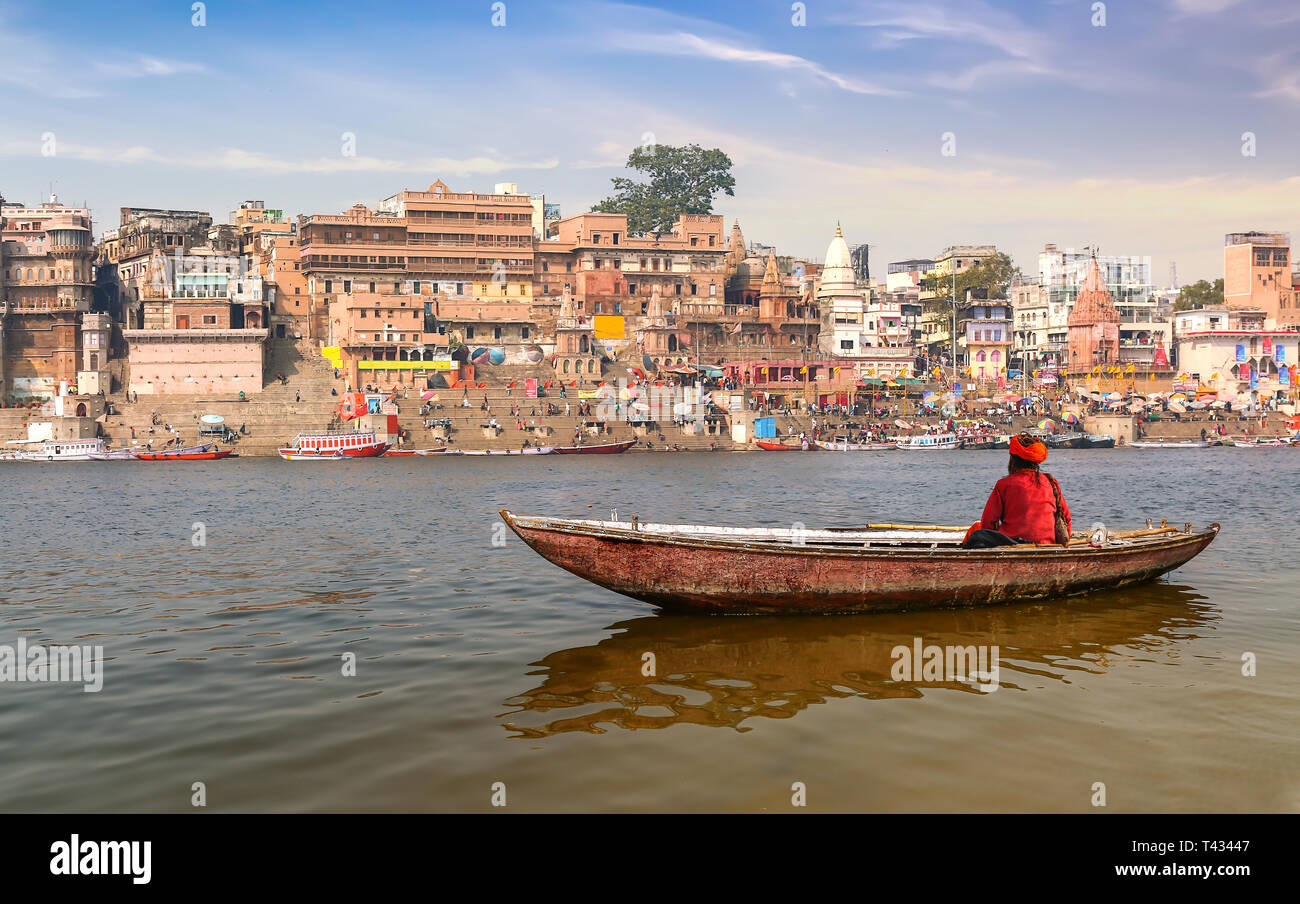 Sadhu on a wooden boat on river Ganges with view of ancient Varanasi city architecture at sunset - Stock Image