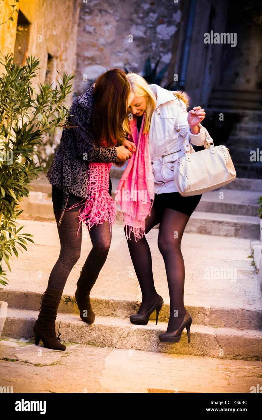 Drunk teenage stumblin'in drunk teen girls laugh walking walk front frontal view full length intoxicated attractive females stilettos stiletto shoes - Stock Image
