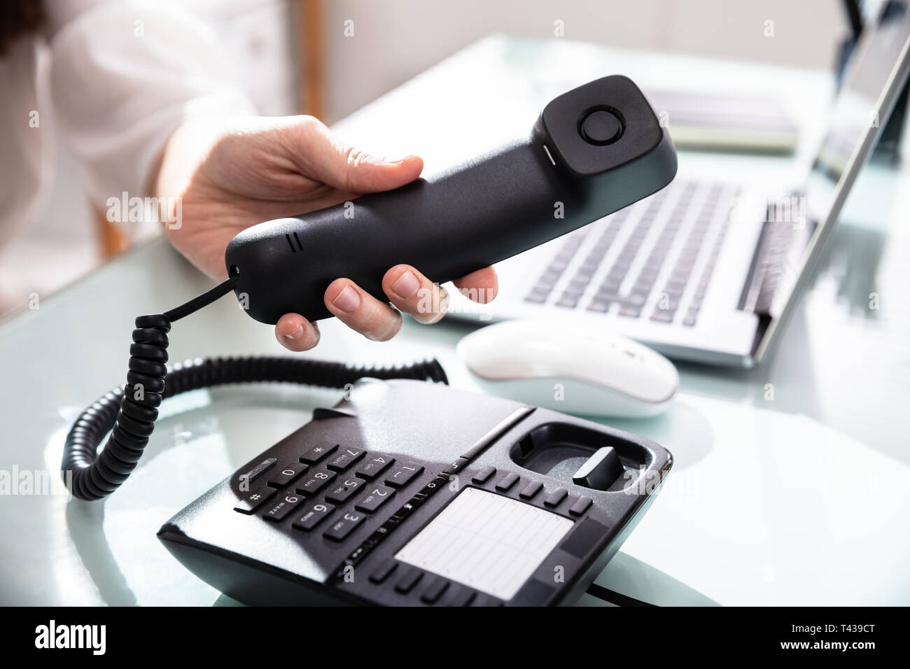Close-up Of A Businesswoman's Hand Dialing Telephone Number To Make Phone Call In Office - Stock Image
