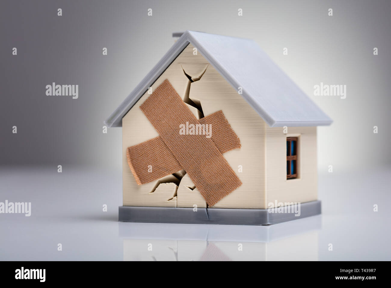 Broken House Model With Crossed Band Aid On Desk - Stock Image