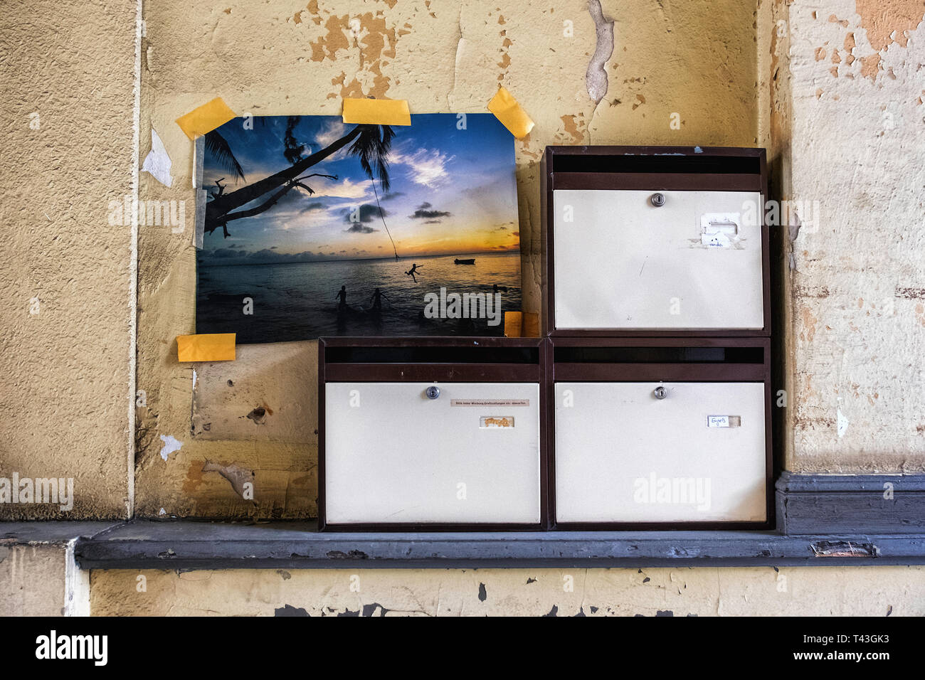Berlin. Old apartment building detail. Peeling weathered wall with new postboxes & photograph taped to wall - Stock Image