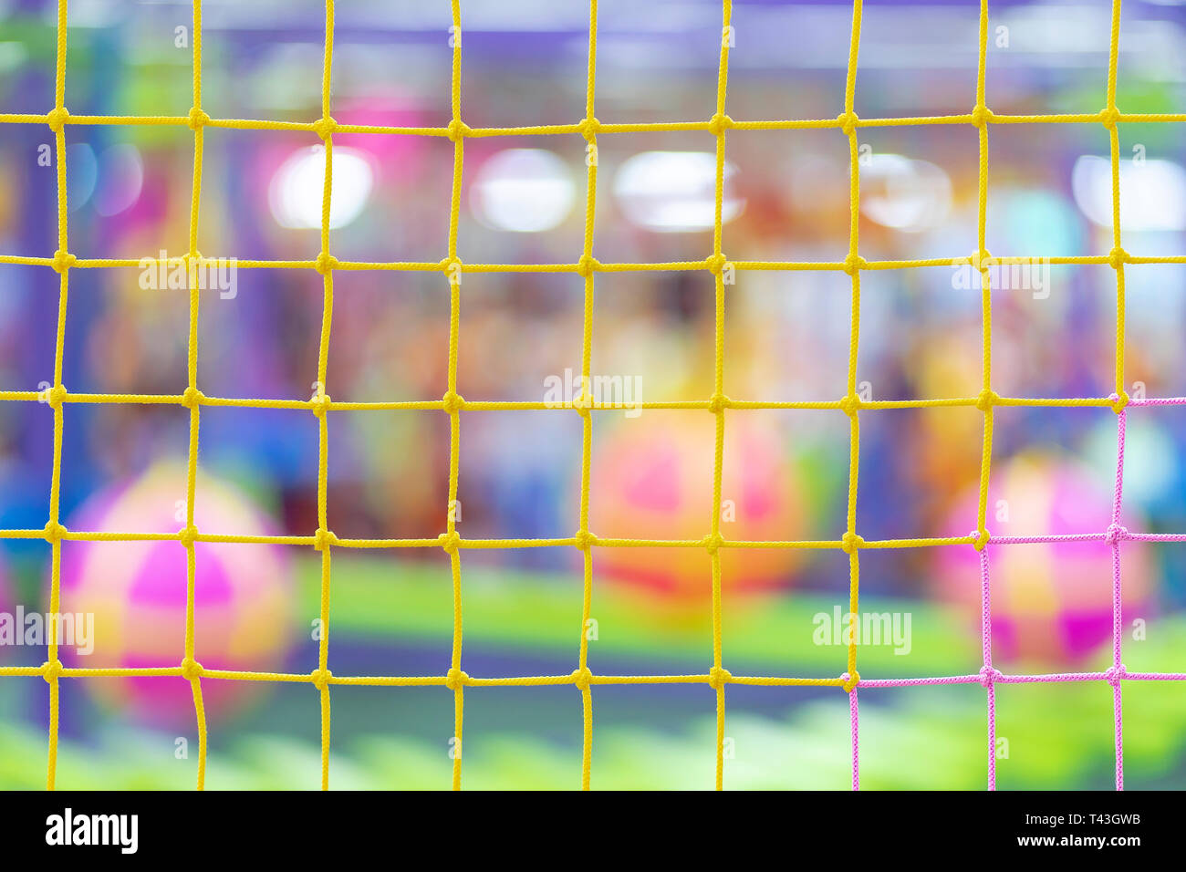 Multi-colored grid on the background of a blurred playground with balls and mazes - Stock Image
