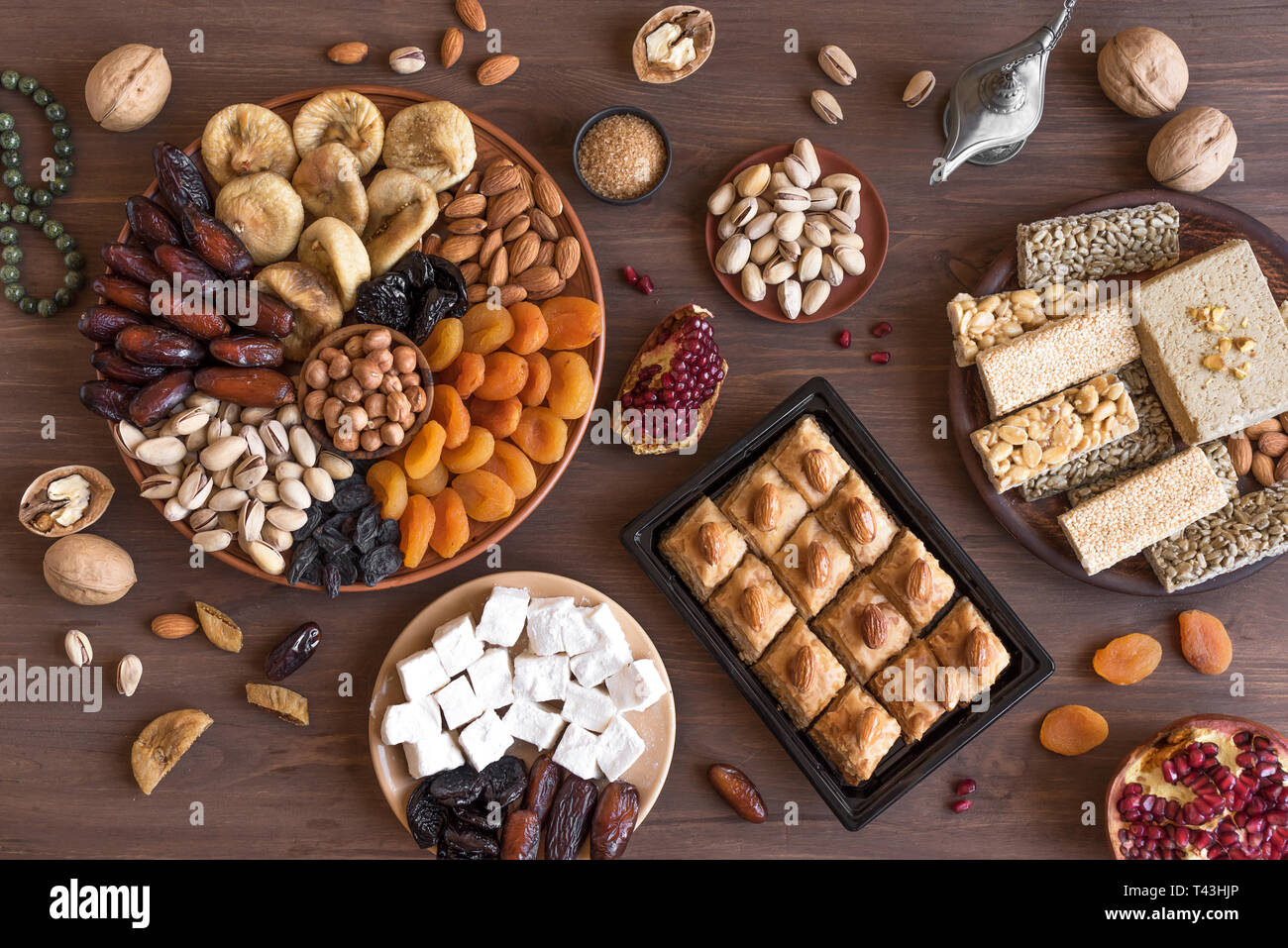 Assortment, set of Eastern, Arabic, Turkish sweets, nuts and dried fruits on wooden table, top view, flat lay. Holiday Middle Eastern traditional swee - Stock Image