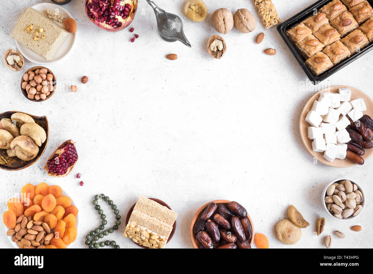 Assortment, set of Eastern, Arabic, Turkish sweets, nuts and dried fruits on white, top view, copy space. Holiday Middle Eastern traditional sweet foo - Stock Image