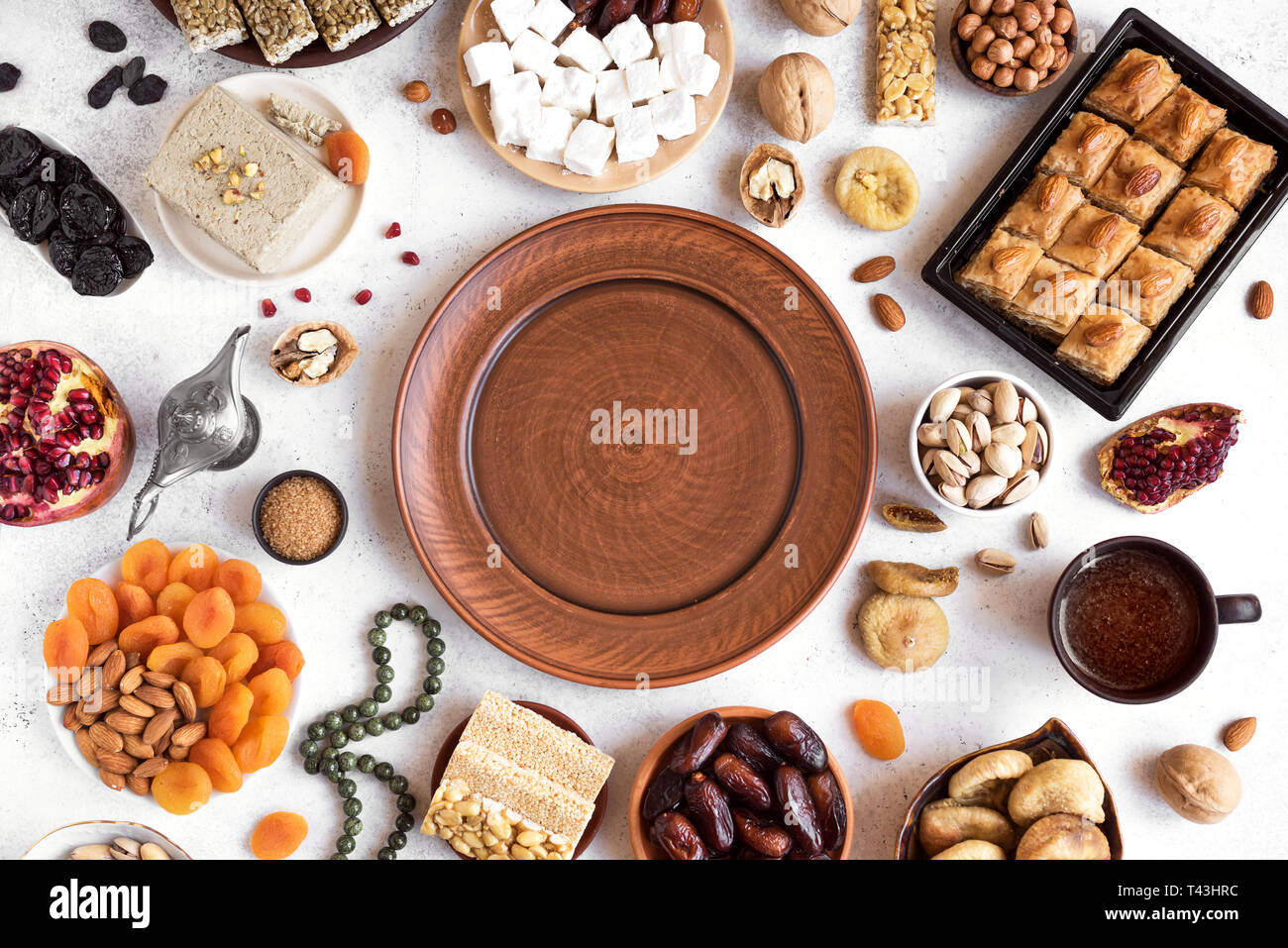Assortment, set of Eastern, Arabic, Turkish sweets, nuts and dried fruits around plate, top view, copy space. Holiday Middle Eastern traditional sweet - Stock Image