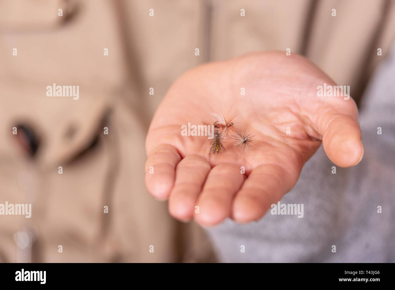 Fisherman showing fishing fly hook in hand palm . Stock Photo