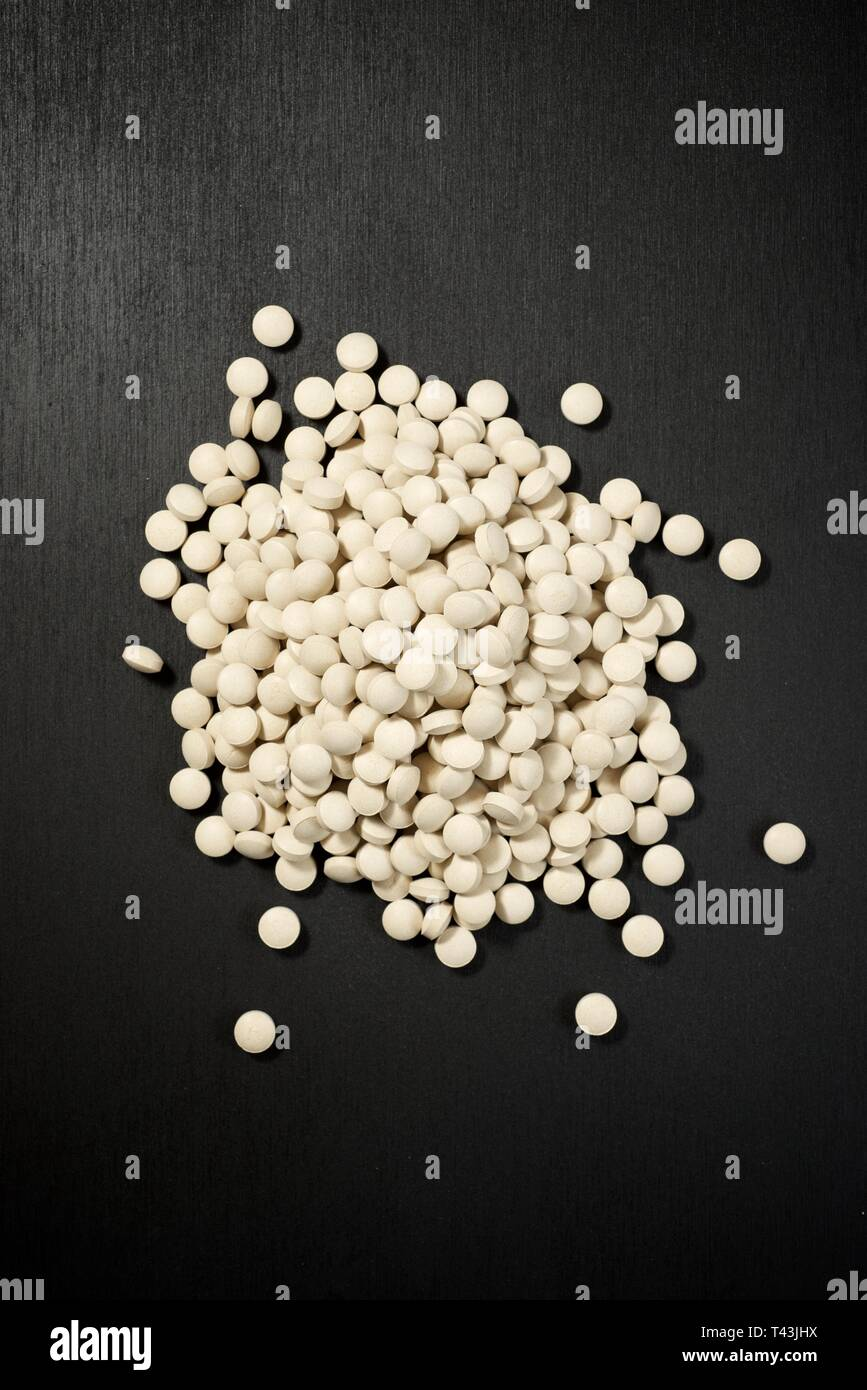 Beer yeast pills on a black table. - Stock Image