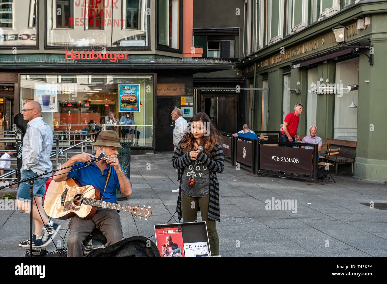 Norway, Oslo. August 1, 2013. Musician and girl singing in the square in Oslo, the capital of Norway. Extra income for . Editorial. - Stock Image