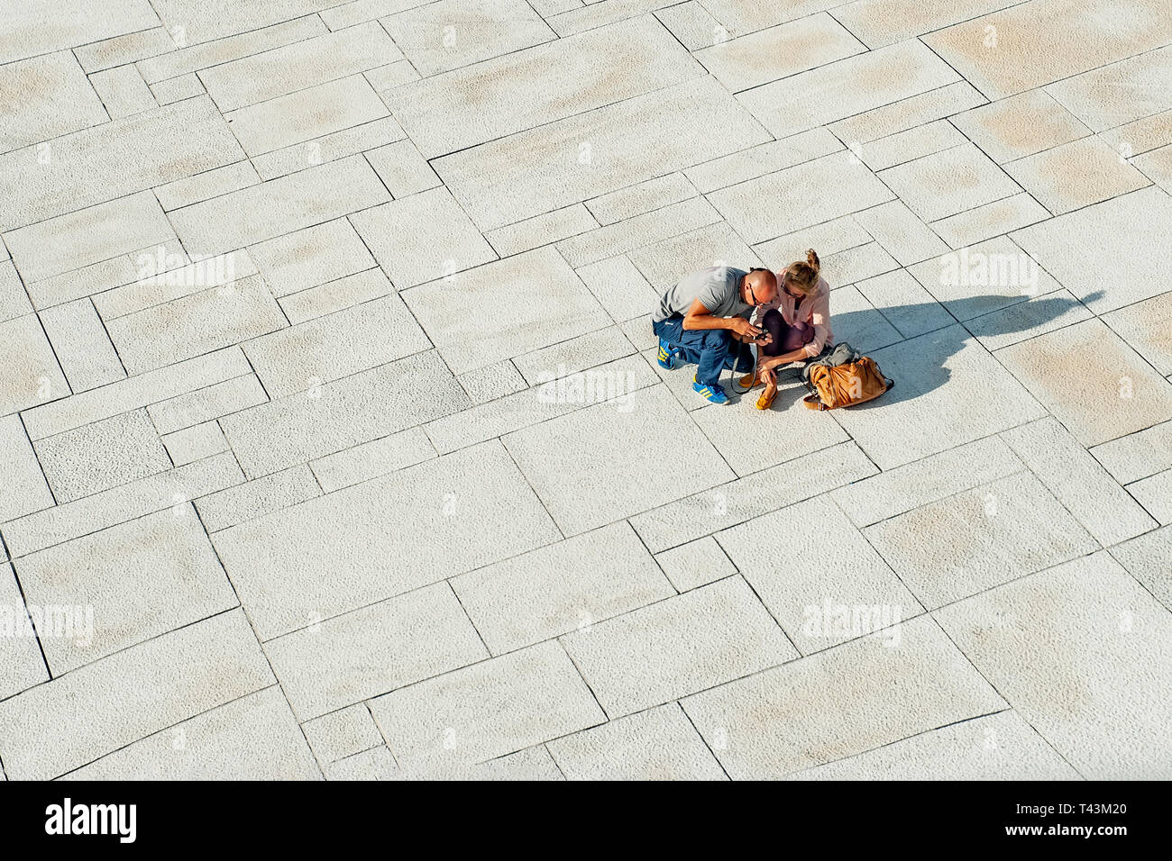 Norway, Oslo August 1, 2013: Two young people tourists relax and view photos on the waterfront of the Opera house in Oslo at sunset. Editorial Stock Photo