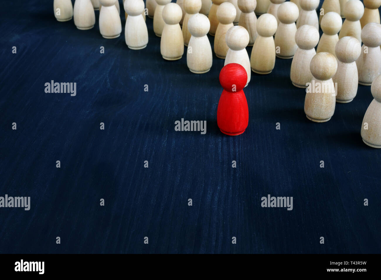 Stand out from the crowd concept. Uniqueness and individuality. Line of figurines. Stock Photo