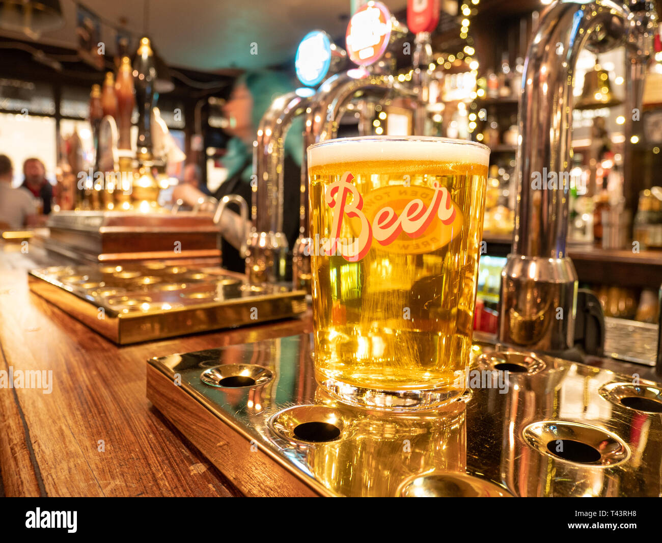 Pint of lager on pub bar, London, UK - Stock Image