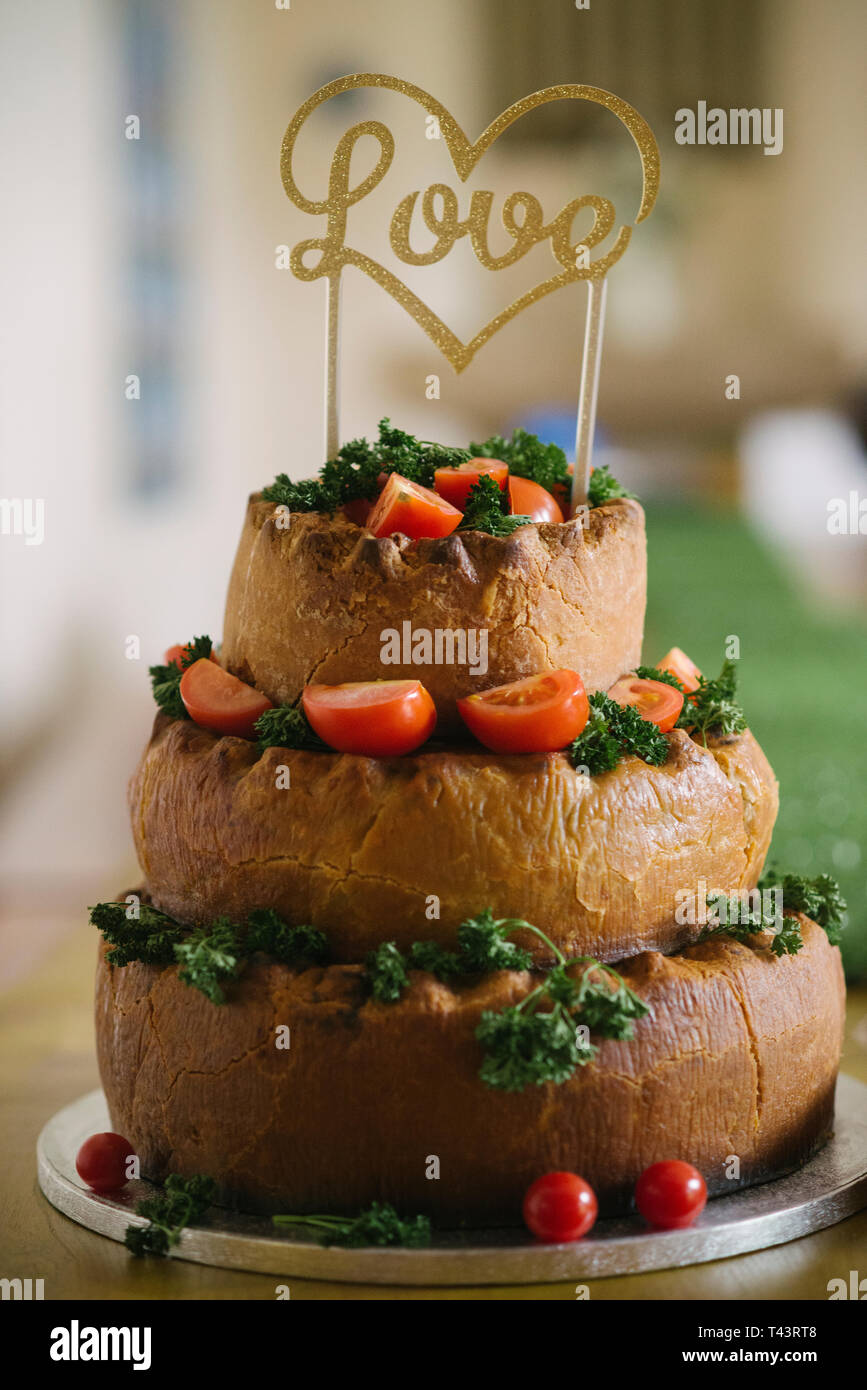 A tiered pork pie wedding cake. Unusual wedding ideas - Stock Image