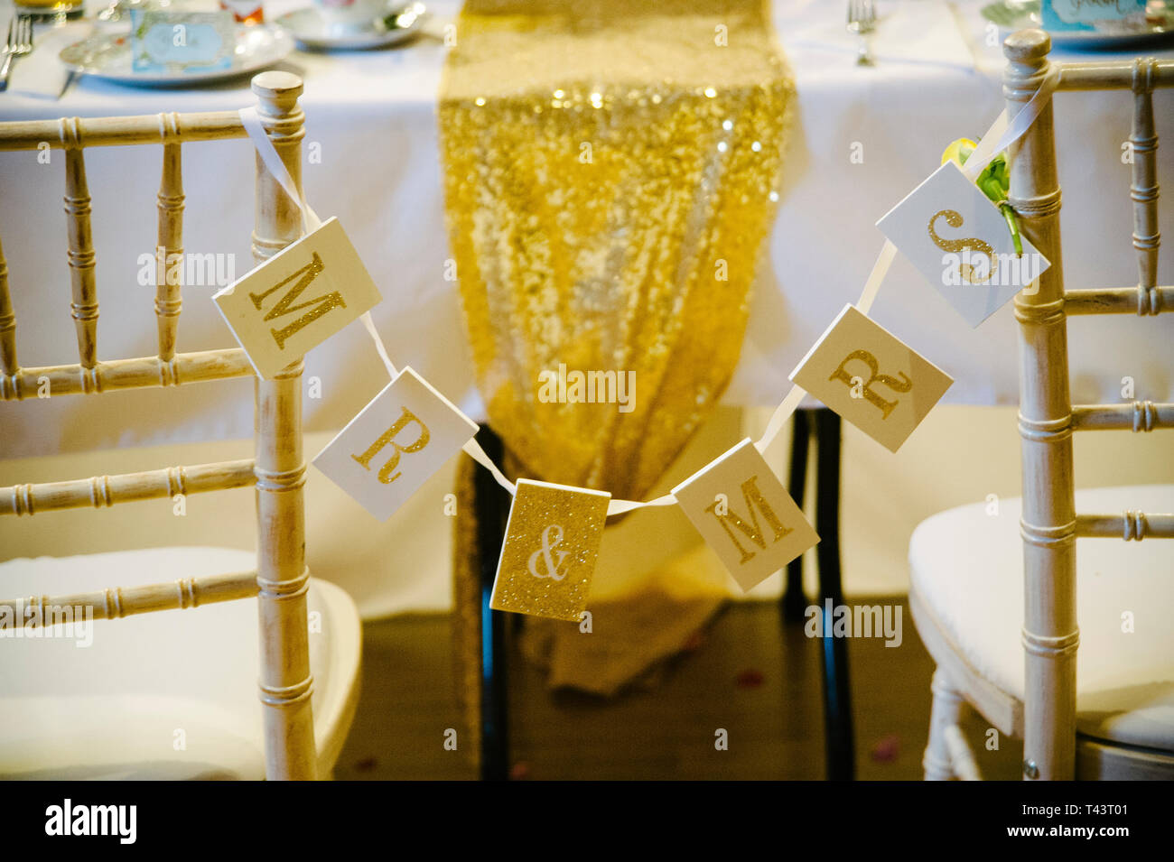 mr & mrs sign bunting tied to wooden chairs at boho wedding reception. Shabby chic wedding ideas - Stock Image