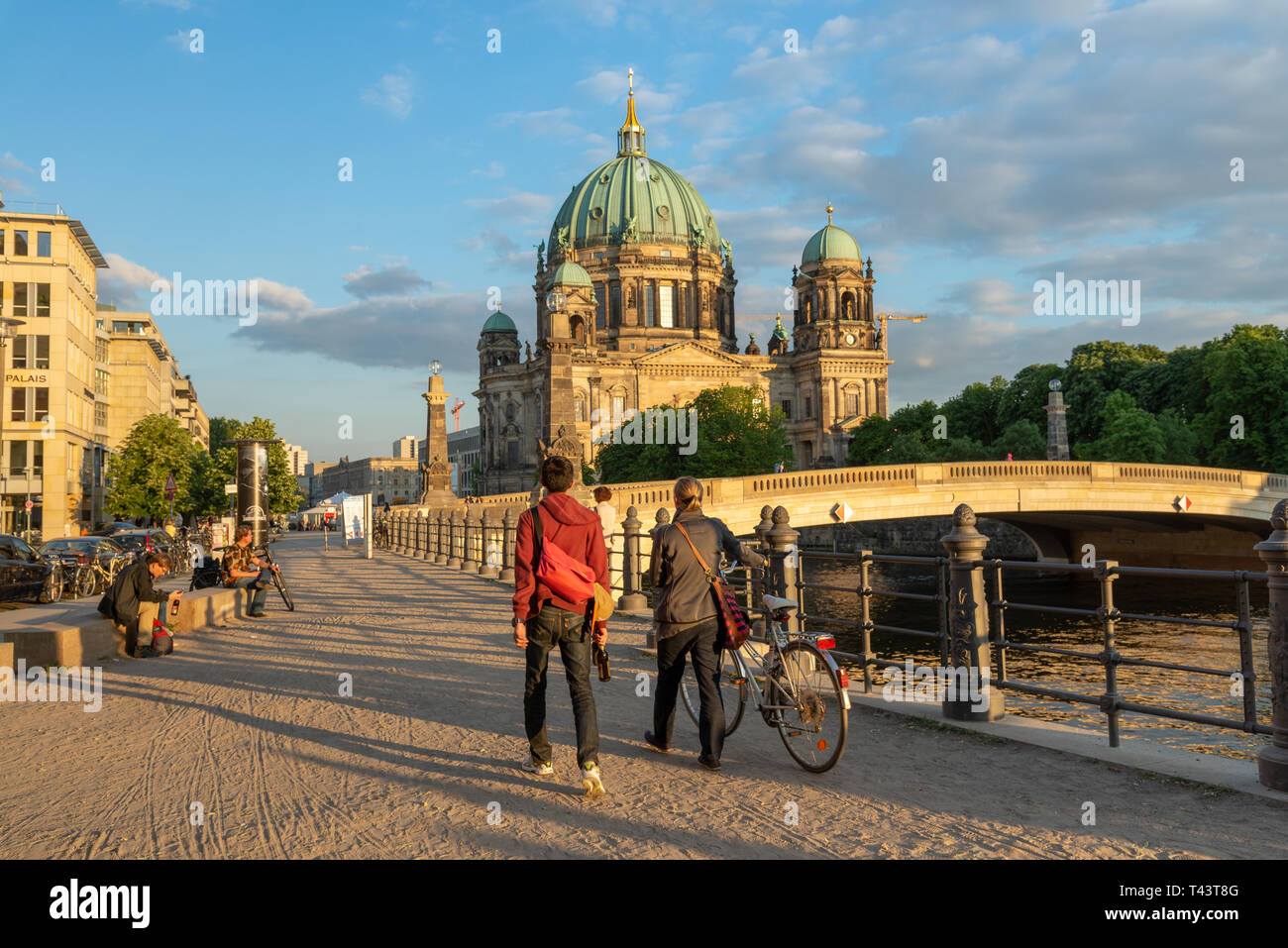 Young couple walking along the banks of the River Spree towards Berlin Cathedral, Mitte, Berlin, Germany - Stock Image