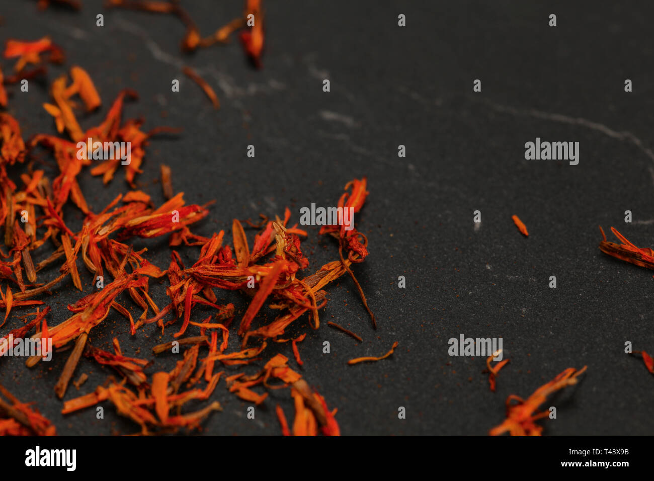 Dried orange red saffron ( Crocus sativus ) flowers on a black board. Space for text in upper right part. Stock Photo