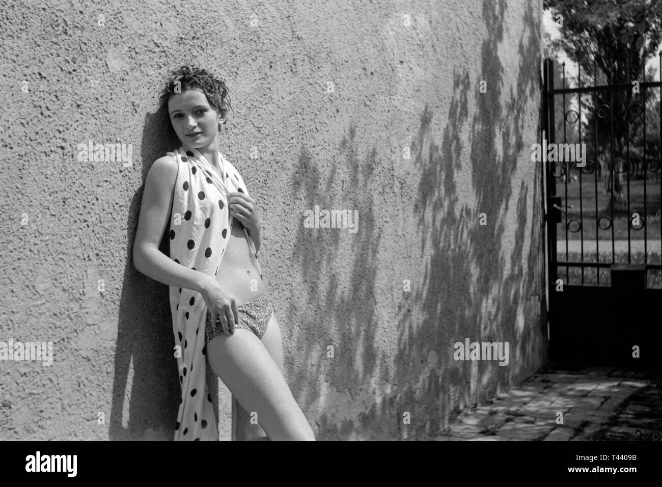 young female leaning against a garden wall wearing a bikini and wrap in the summer sunshine 1970s hungary - Stock Image