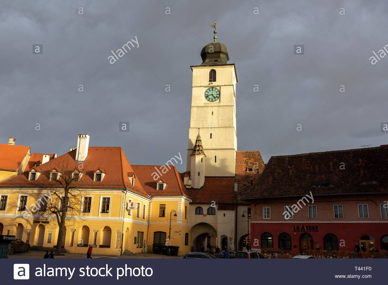 Sunlight Falls Across the Clock Tower of Cisnădiei Gate During Sunset - Sibiu, Romania - Stock Image