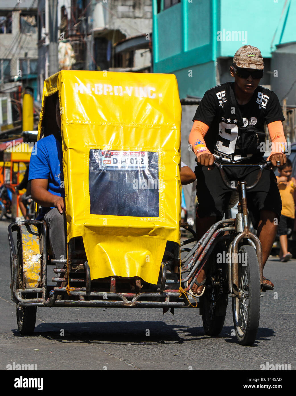 A local transport pedicab (rickshaw) driver with his passenger traverse a street in Manila, Philippines. - Stock Image