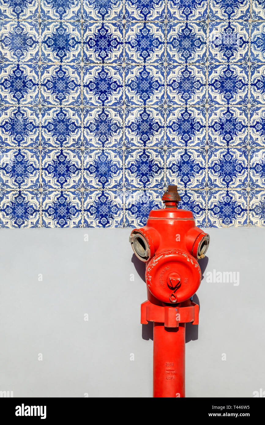 Red fire hydrant in front of a tiled wall in Lisbon, Portugal - Stock Image