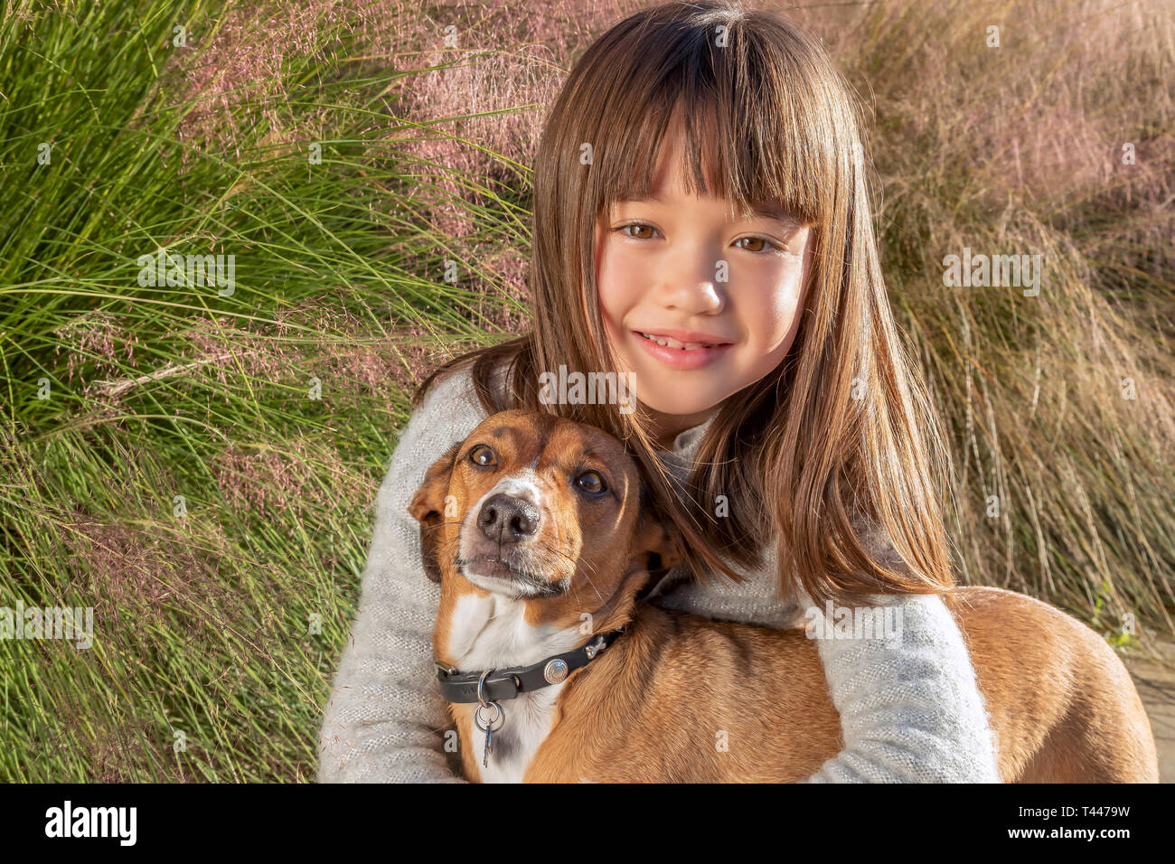 Seven year old girl with her dog in the park - Stock Image