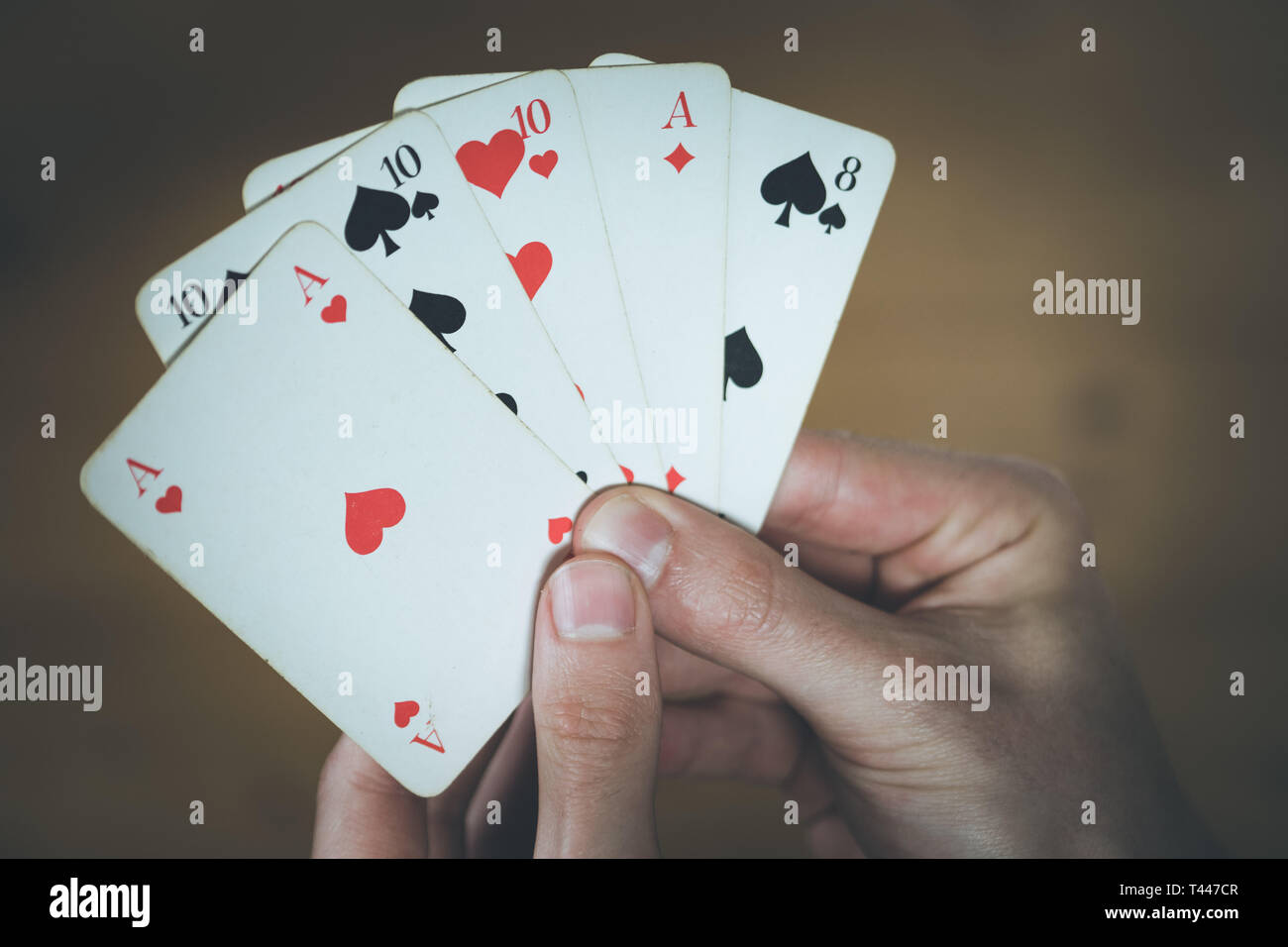 Man is playing cards, cutout of his hands - Stock Image