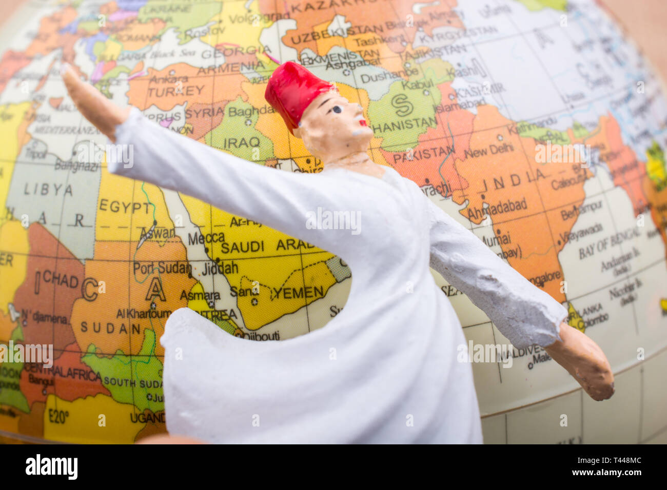Swirling dervish in front of a globe on a textured background - Stock Image