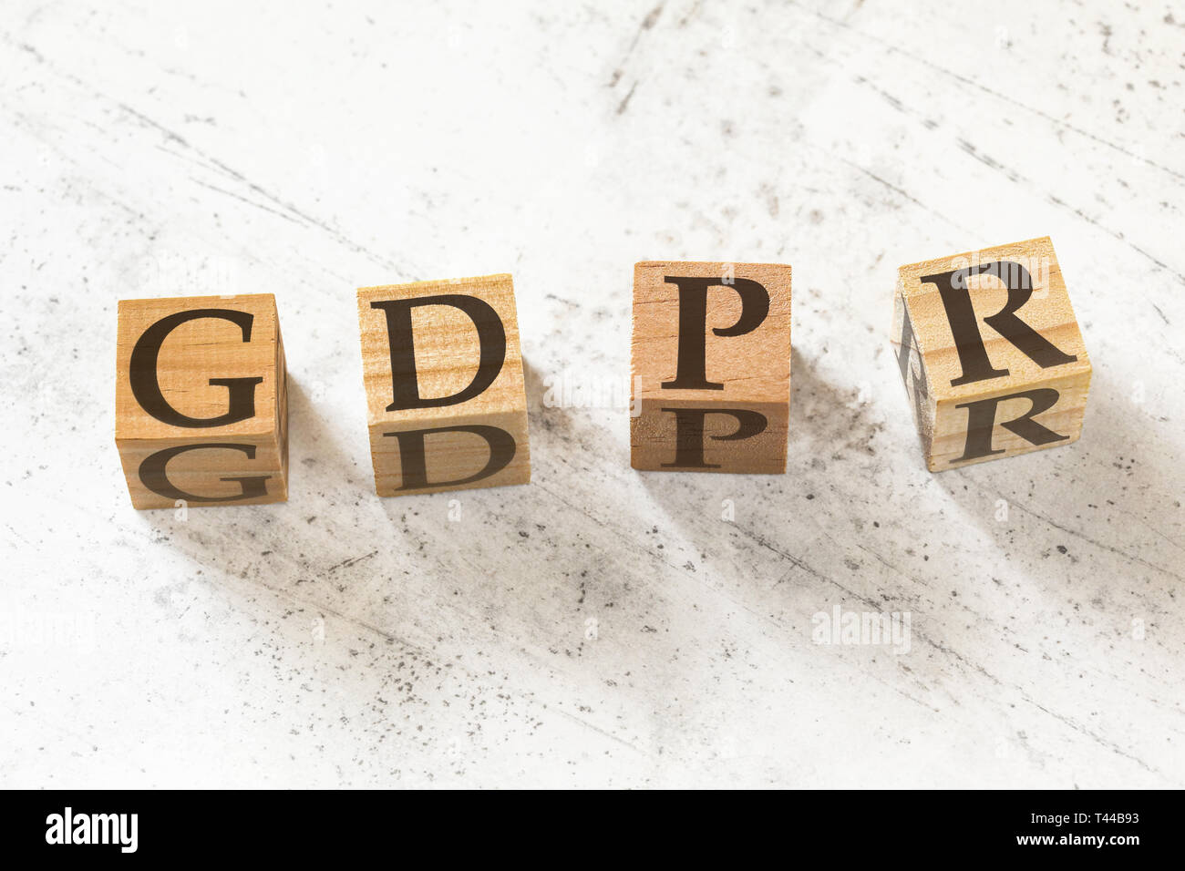 Four wooden cubes with letters GDPR meaning General Data Protection Regulation on white working board. - Stock Image