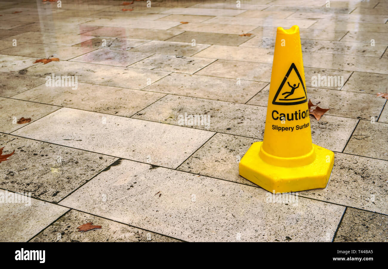 Yellow cone with caution slippery surface sign, on wet pavement tiles. - Stock Image