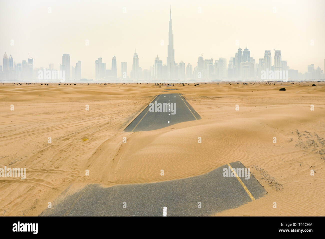 View from above, stunning aerial view of a deserted road covered by sand dunes in the middle of the Dubai desert. - Stock Image