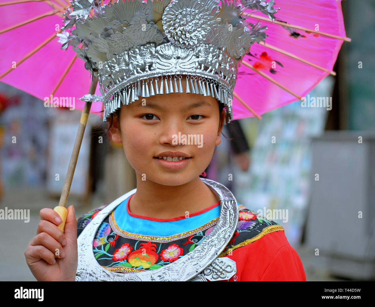 Pretty Chinese pre-teen girl with a pink paper parasol wears a traditional Miao headdress with silver accessories and smiles for the camera. - Stock Image