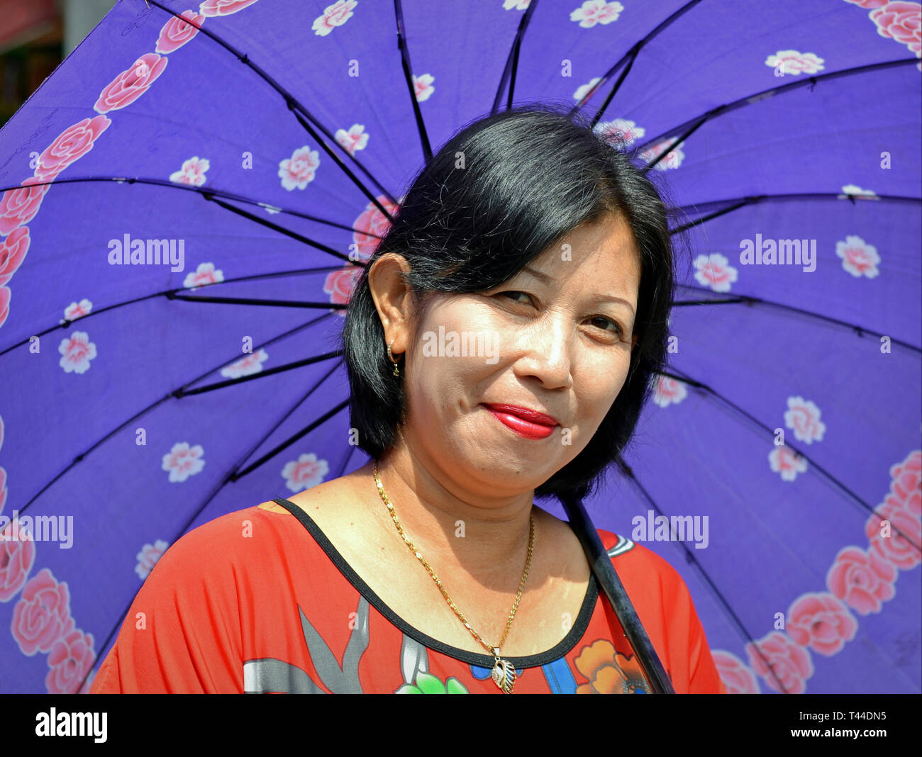 Indonesian woman from Central Kalimantan uses her blue umbrella as sunshade. - Stock Image