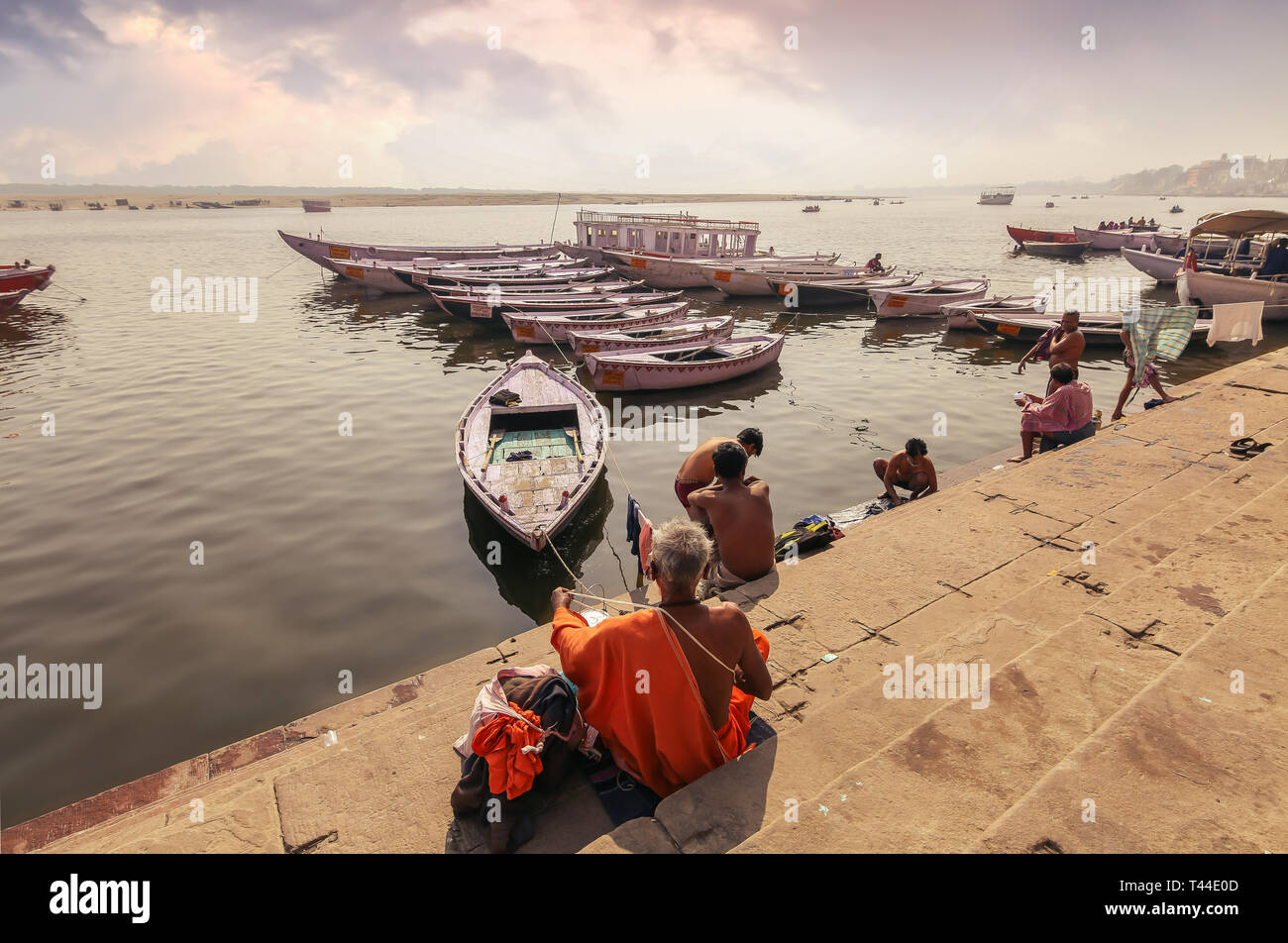 Varanasi Ganges river bank with view of wooden boats and sadhu baba sitting on the stairway. - Stock Image