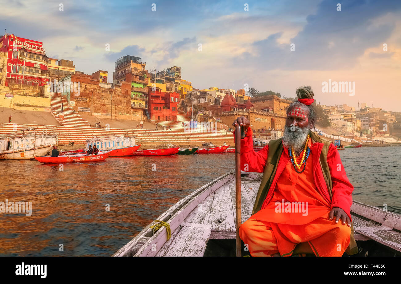 Sadhu baba sitting on a wooden overlooking ancient Varanasi city architecture with Ganges river ghat at sunset. - Stock Image