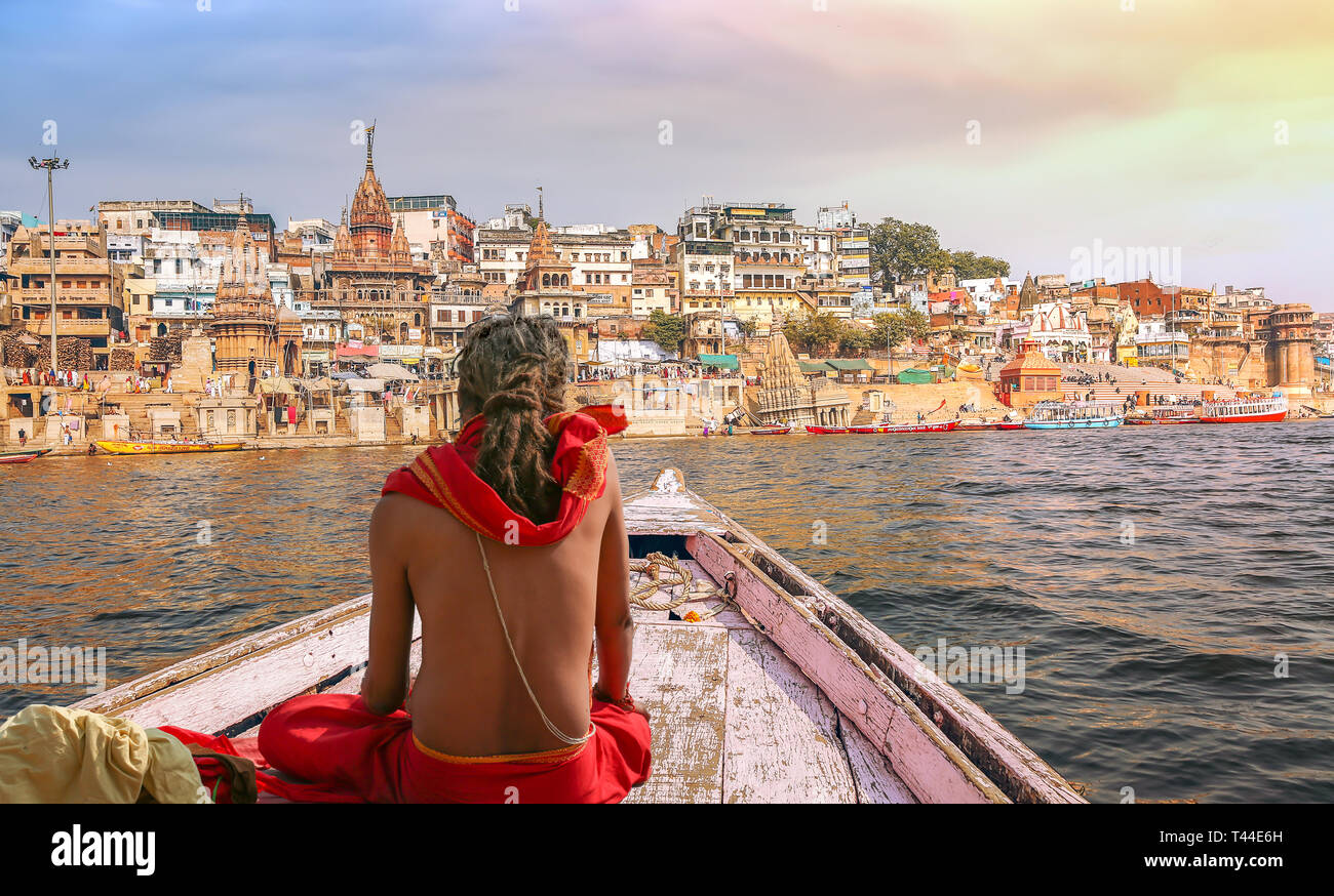 Varanasi city architecture with Ganges river bank at sunset with view of sadhu baba enjoying a boat ride on river Ganges. - Stock Image
