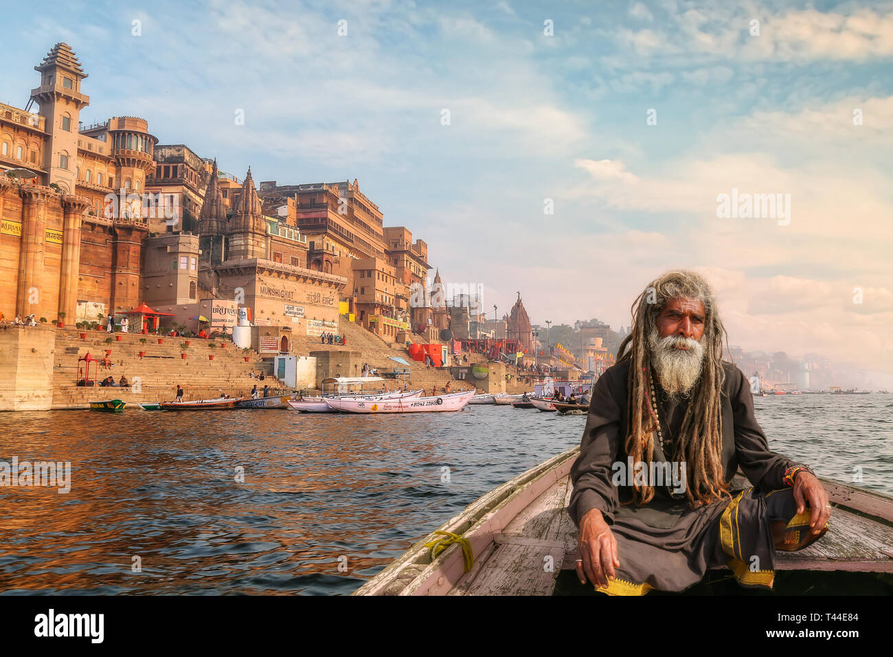 Sadhu baba on a wooden boat overlooking the historic Varanasi city and Ganges river ghats, India. - Stock Image