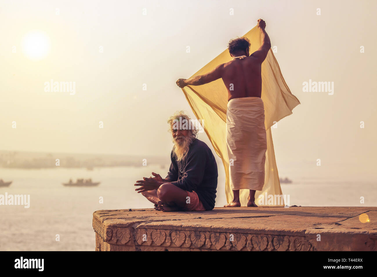 Aged man prepares for meditation while a pilgrim dries his clothes at Varanasi Ganges river ghat on foggy winter morning - Stock Image