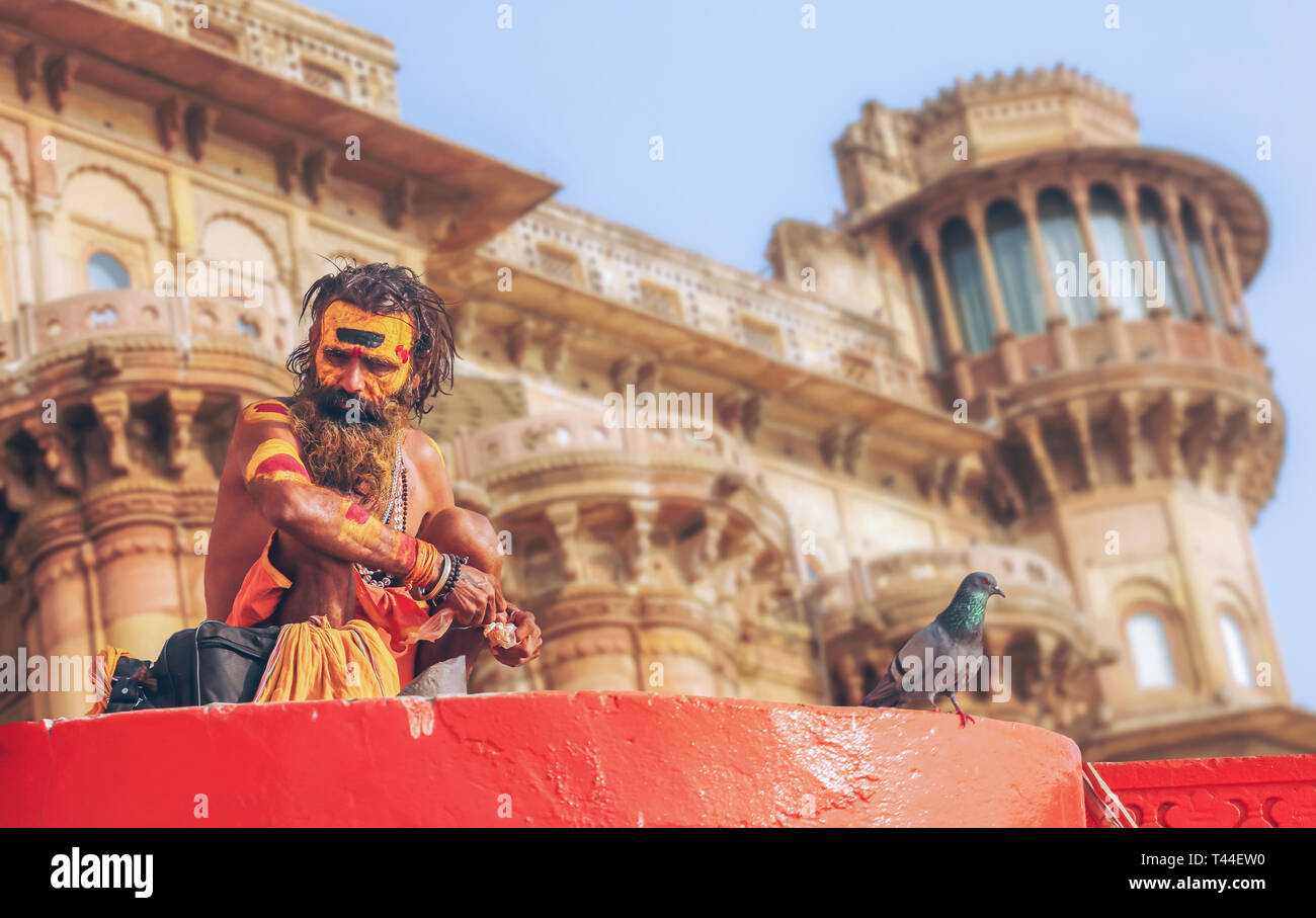 Sadhu baba sitting at Varanasi Ganges ghat with ancient architecture building as the backdrop. - Stock Image
