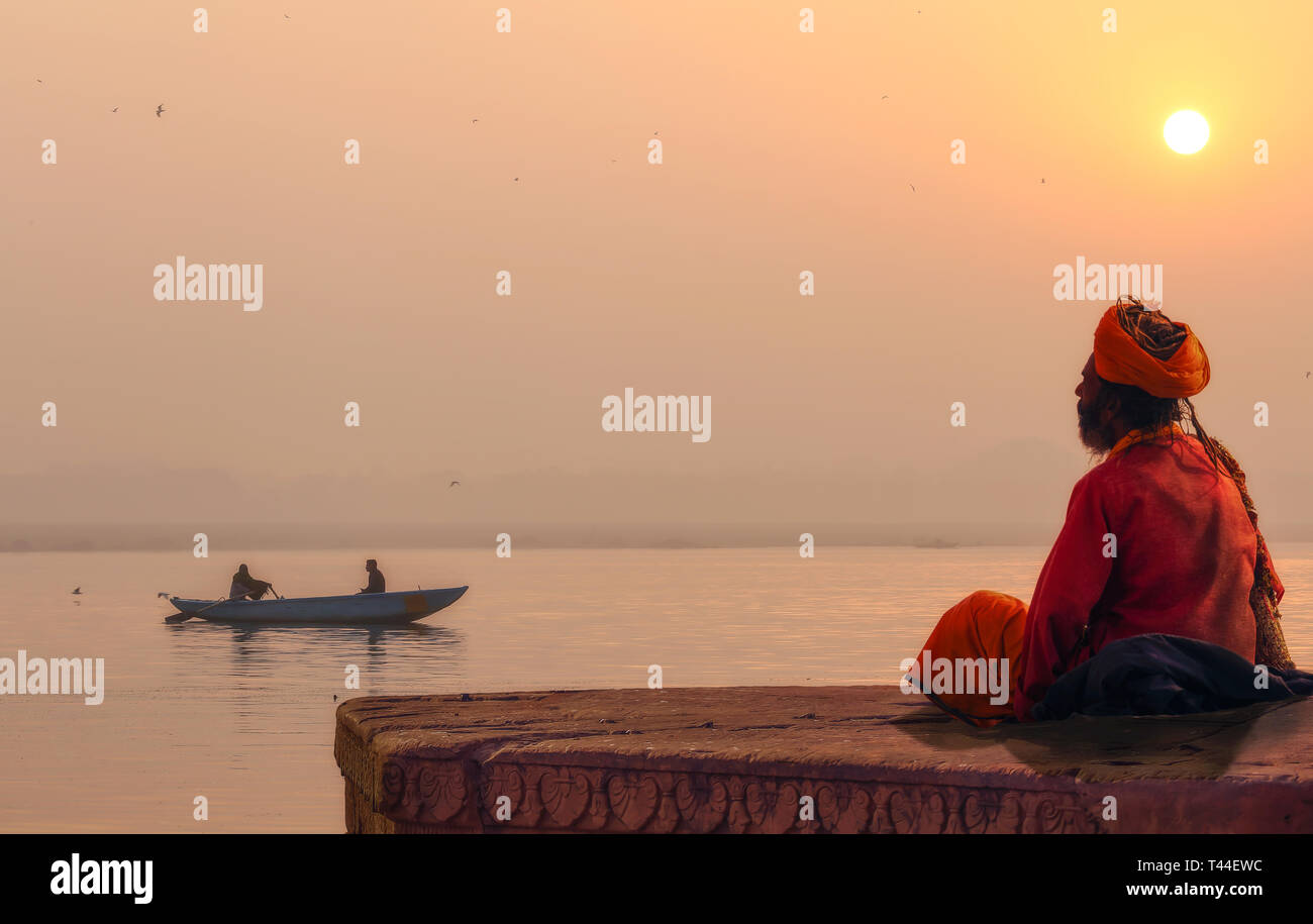 Hindu sadhu baba in meditation at the Ganges river bank at sunrise with view of a wooden boat on river Ganga - Stock Image