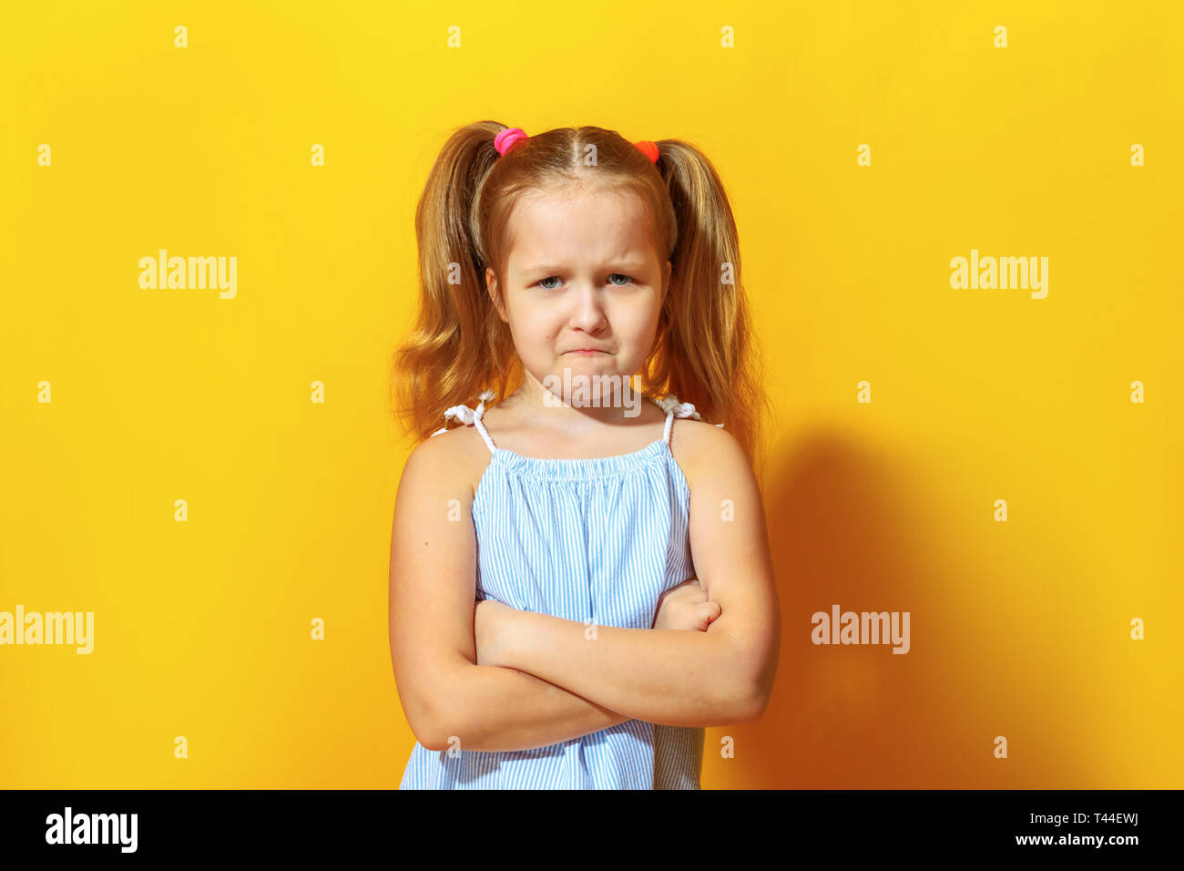 Closeup portrait of upset little girl on yellow background. The child crossed his arms and pouted his lips. - Stock Image