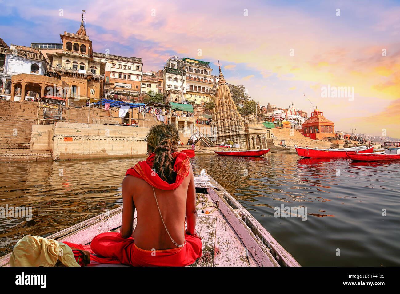 Varanasi city architecture with Ganges river bank at sunset with view of sadhu baba enjoying a boat ride on river Ganga. - Stock Image