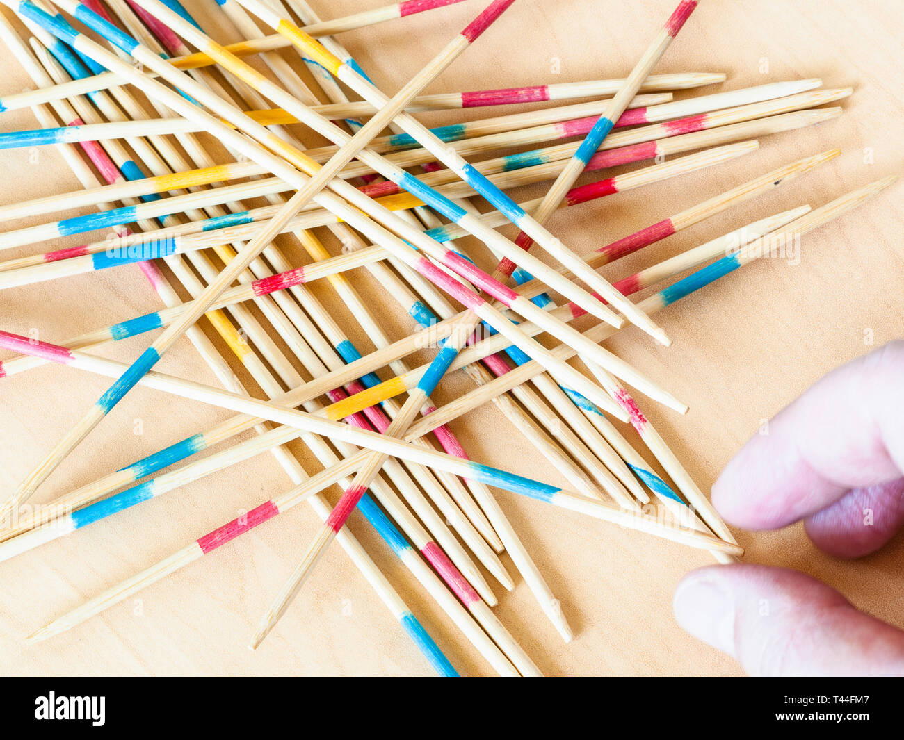 player picks up a stick from pile in Mikado game close up on wood board - Stock Image