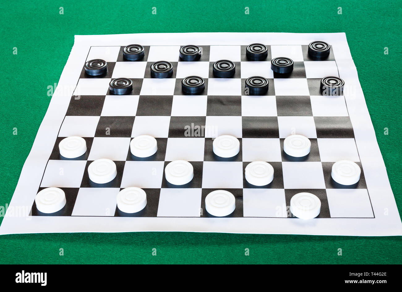 Draughts On Black And White Checkered Sheet Board On Green Baize