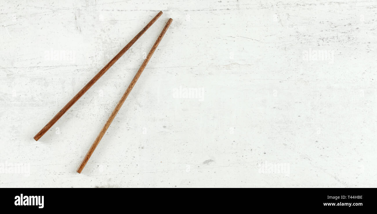 Top down view - pair of dark wood chopsticks on white board. Can be used as banner for asian / chinese food, space for text on right. Stock Photo