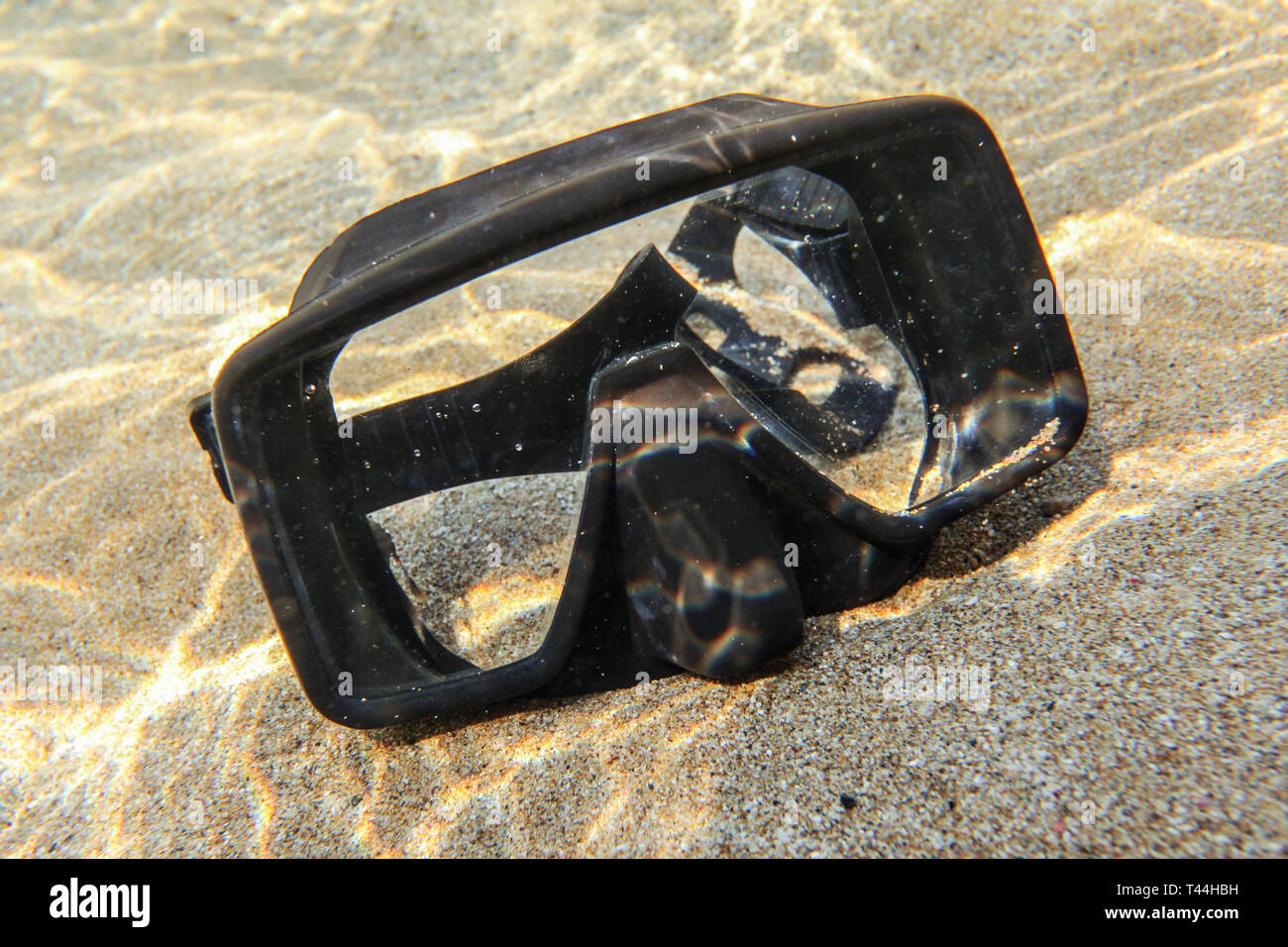 Underwater photo - sun shining to rubber black diving mask on sand in shallow water. Stock Photo
