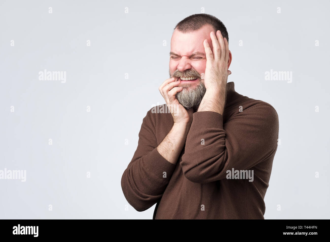 man feeling pain suffering from bad toothache. - Stock Image