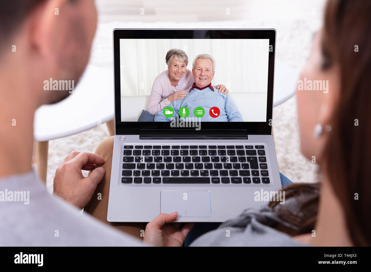 Close-up Of An Couple Video Conferencing With Their Happy Parents On Laptop - Stock Image